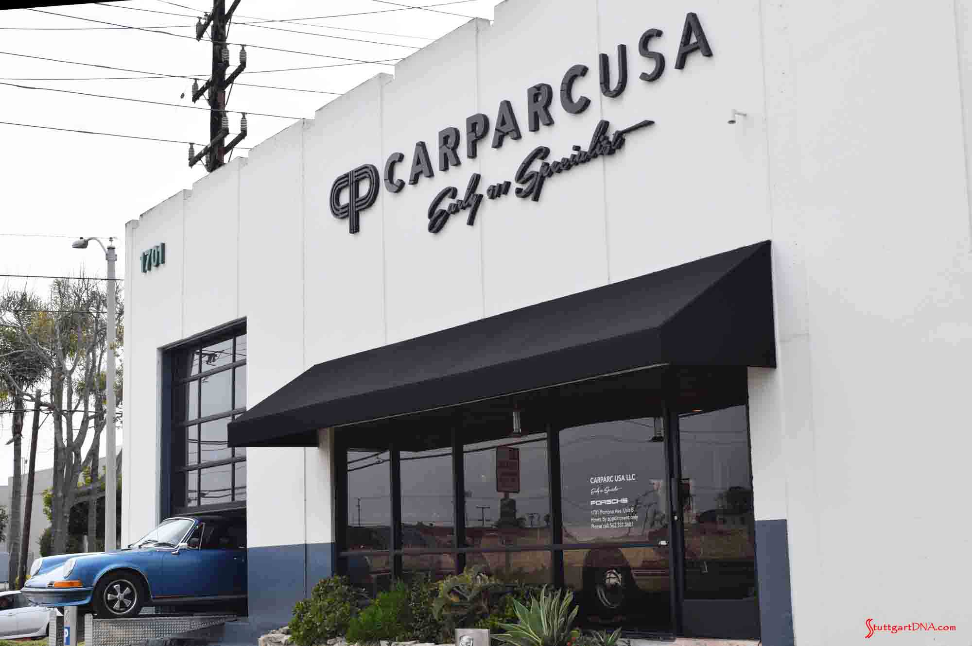 Pictured here is the Carparc USA facade during the 2017 Porsche L.A. Lit Meet Weekend., with signage out front up high and a blue 911 Targa extending out front through the open garage door in b.g. Credit: StuttgartDNA