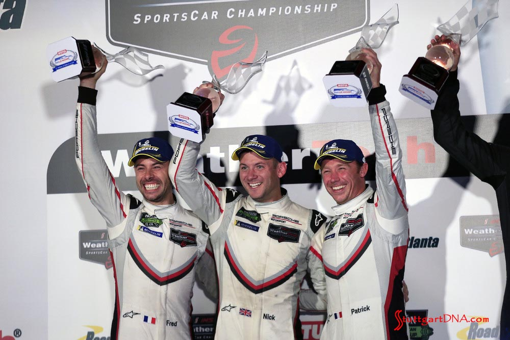 Porsche wins 2018 Petit Le Mans: pictured here are the ecstatic Makowiecki, Tandy and Pilet celebrating at the top of 2018 Petit Le Mans podium, with first-place trophies in hand, held high above their heads. Credit: Porsche AG