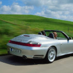 996-gen Porsche 911 Buyer Guide: Seen here is a 996-gen Porsche 911 Carrera 4S arctic-silver Cabriolet, from right-rear angle, at speed on a picturesque country road with a pretty woman in the passenger seat. Credit: Porsche AG