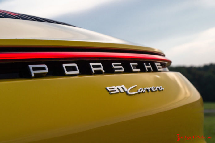 """October 2019 USA Sales: This photo is a tight shot of the rear """"Porsche 911 Carrera"""" badging and illuminated continuous red taillight strip on a Racing Yellow 911. Credit: Porsche AG"""