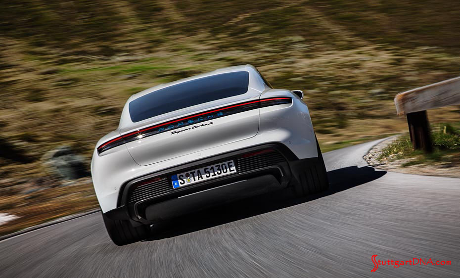 Porsche Taycan first electric sports car world premiere: A white Taycan Turbo S is seen from the right-rear at speed, carving the curves on a twisty road. Credit: Porsche AG
